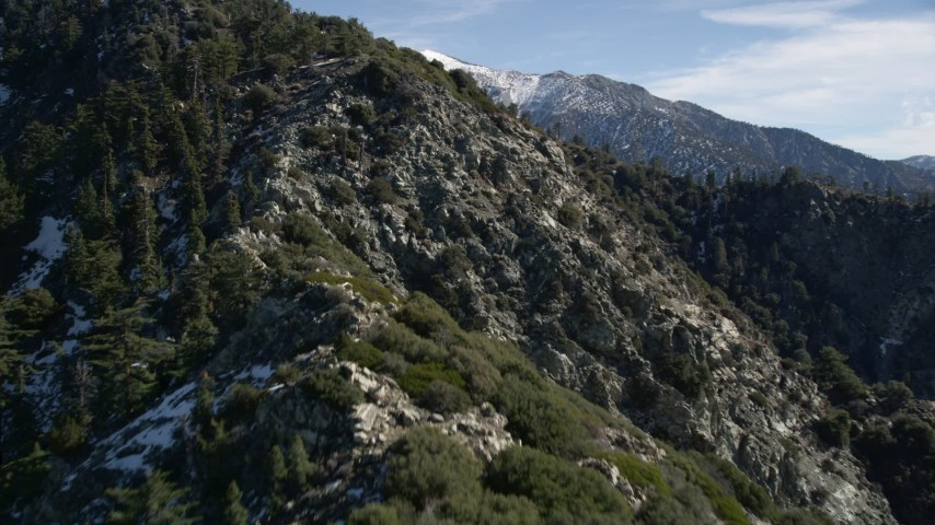 5K stock footage aerial video approach and fly over slope with light snow in the San Gabriel Mountains, California Aerial Stock Footage | AX0009_049E