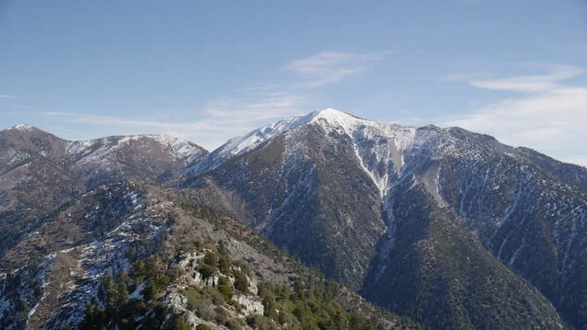 5K stock footage aerial video fly over trees and snow to reveal snowy peak in the San Gabriel Mountains in Winter, California Aerial Stock Footage | AX0009_052