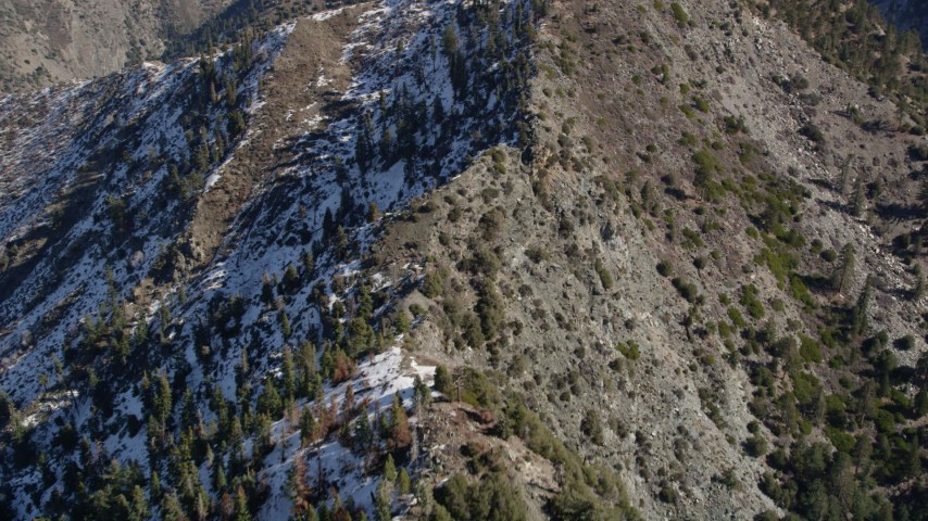 5K stock footage aerial video fly over ridge with snow on shady side in the San Gabriel Mountains in winter, California Aerial Stock Footage | AX0009_053