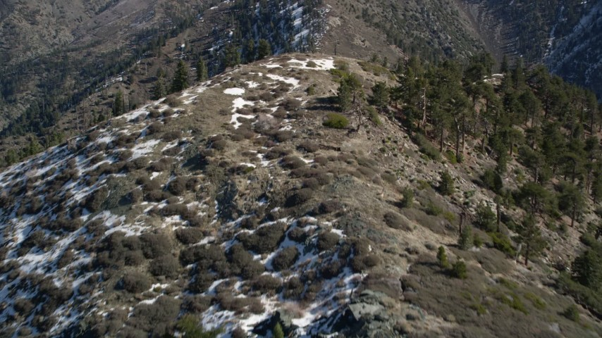 5K stock footage aerial video fly over ridge with snow on shady side in the San Gabriel Mountains in winter, California Aerial Stock Footage | AX0009_053E