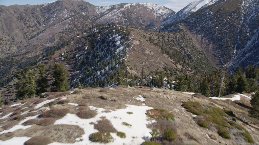 5K stock footage aerial video of ridge with snow and tilt to reveal peaks San Gabriel Mountains in winter, California Aerial Stock Footage | AX0009_054
