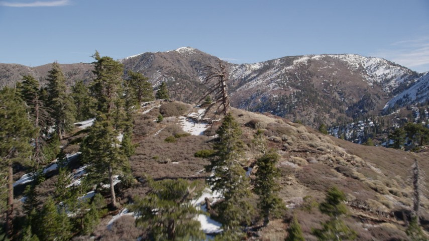 5K stock footage aerial video fly over ridge to approach mountains with light snow in the San Gabriel Mountains in winter, California Aerial Stock Footage   AX0009_056