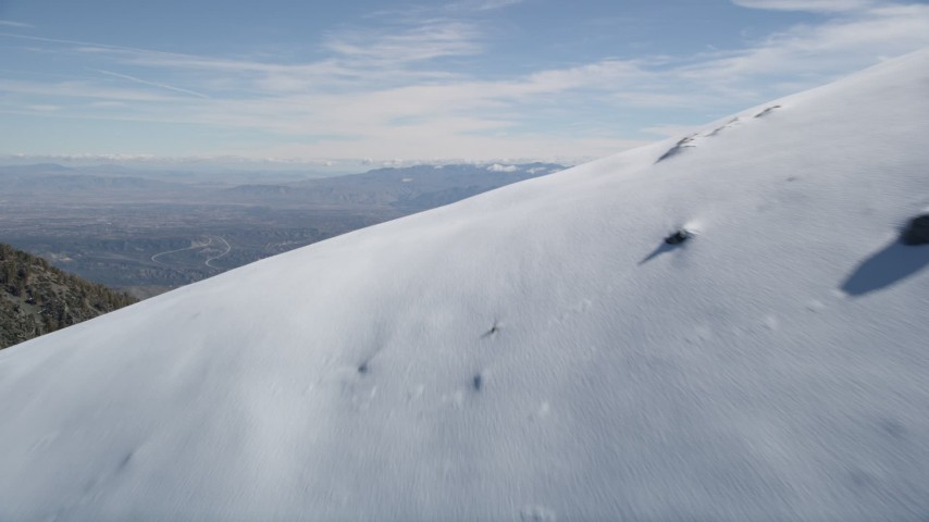 5K stock footage aerial video fly over snowy slope to reveal smaller mountains in the San Gabriel Mountains, California Aerial Stock Footage | AX0009_061