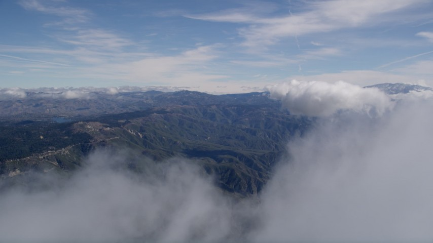 5K aerial video fly through a small cloud to reveal the San Bernardino Mountains, California Aerial Stock Footage AX0009_074