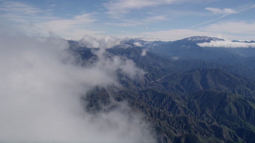 5K aerial video of flying over a misty cloud to reveal the San Bernardino Mountains of California Aerial Stock Footage   AX0009_076