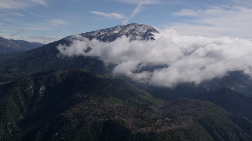 5K stock footage aerial video of approaching clouds near a snowy peak in the San Bernardino Mountains, California Aerial Stock Footage   AX0009_086