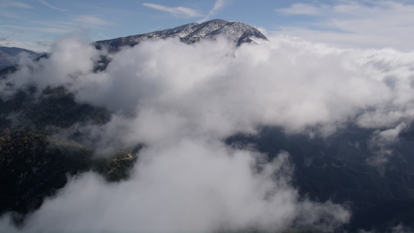 5K stock footage aerial video approaching cloud cover near a frozen peak in the San Bernardino Mountains Aerial Stock Footage | AX0009_088