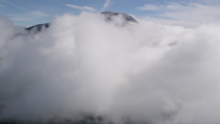 5K aerial video fly over a cloud near a peak with winter snow in the San Bernardino Mountains, California Aerial Stock Footage   AX0009_089