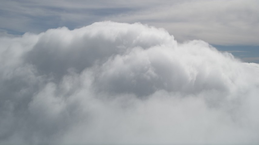5K aerial video fly over thick clouds to reveal summit of San Bernardino Mountains peak, California Aerial Stock Footage | AX0009_101
