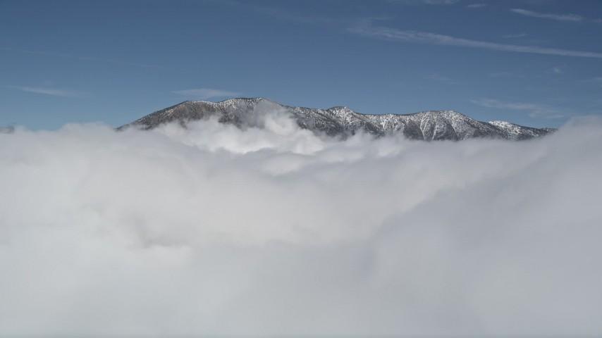 5K stock footage aerial video orbit clouds to reveal snowy summits in San Bernardino Mountains in winter, California Aerial Stock Footage | AX0009_105