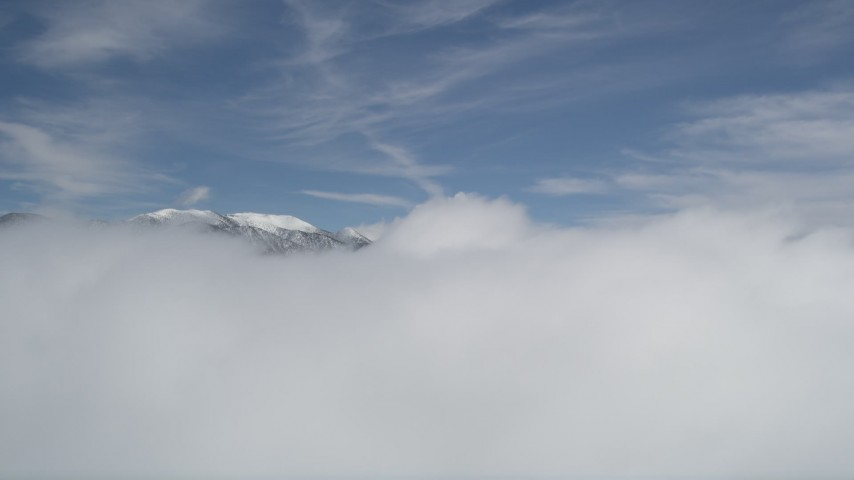 5K stock footage aerial video of snowy San Bernardino Mountains beyond thick clouds in winter, California Aerial Stock Footage   AX0009_106