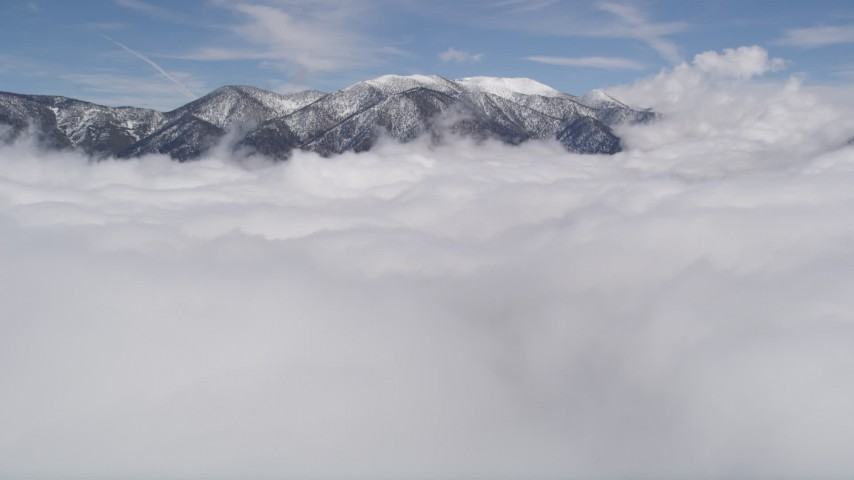 5K aerial video tilt up from clouds to reveal snowy San Bernardino Mountains, California Aerial Stock Footage | AX0009_108
