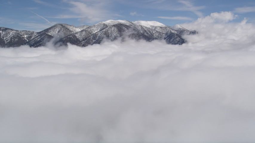 5K aerial video fly low over clouds toward snowy San Bernardino Mountains in winter, California Aerial Stock Footage | AX0009_109