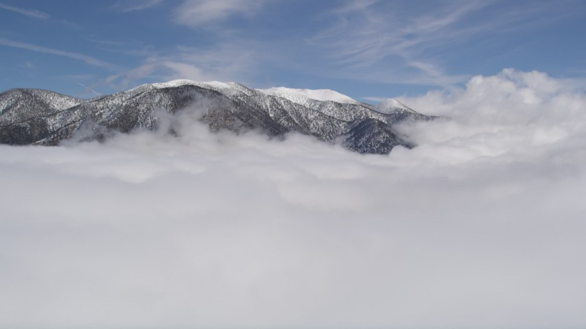 5K aerial video approach snowy San Bernardino Mountains and fly over clouds in winter, California Aerial Stock Footage | AX0009_110