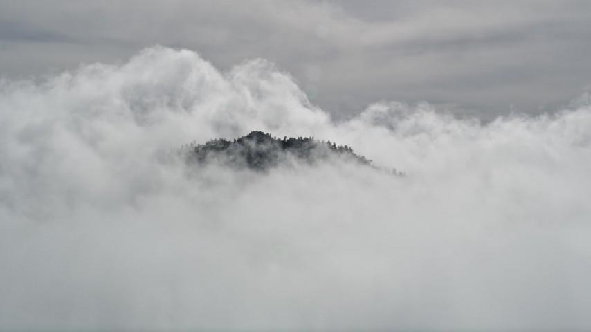 5K stock footage aerial video orbit San Bernardino Mountains peak poking through clouds, California Aerial Stock Footage   AX0009_112