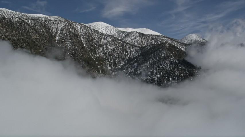 5K stock footage aerial video of approaching San Bernardino Mountains ridge with winter snow, California Aerial Stock Footage   AX0009_113