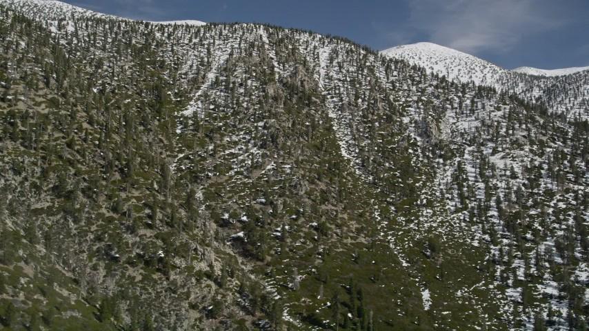 5K stock footage aerial video tilt up a San Bernardino Mountains slope with light winter snow, California Aerial Stock Footage   AX0009_115