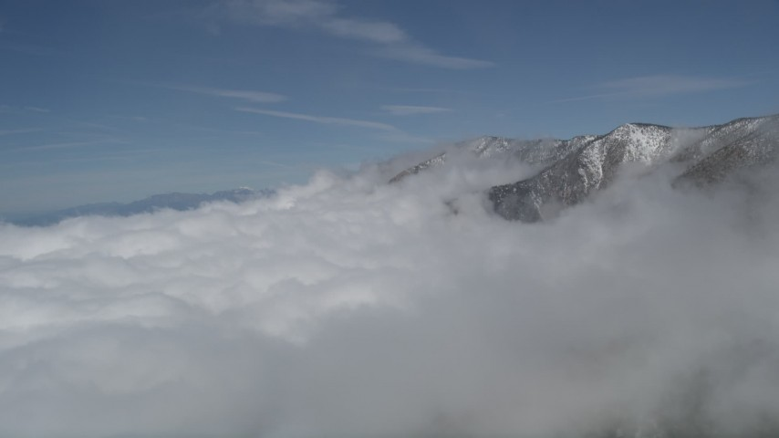 5K stock footage aerial video flyby clouds to reveal San Bernardino Mountains with winter snow, California Aerial Stock Footage | AX0009_116