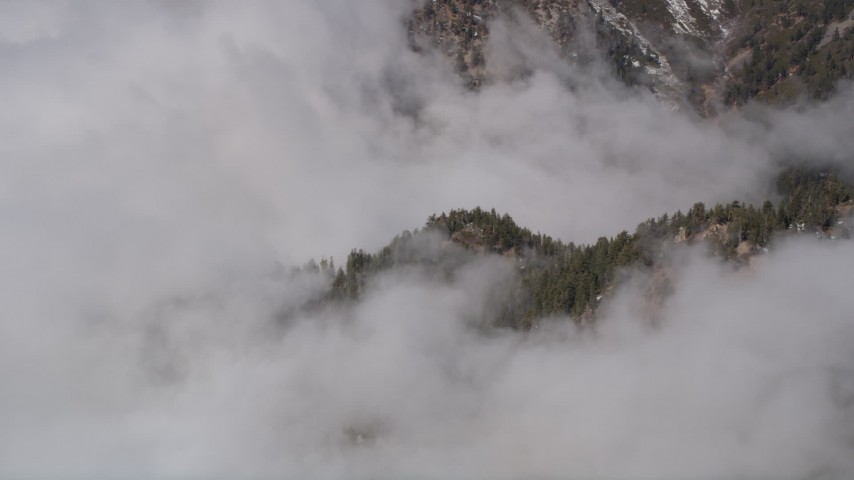 5K aerial video approach the San Bernardino Mountains shrouded in clouds, California Aerial Stock Footage | AX0009_117