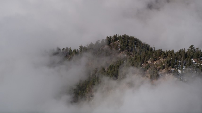 5K stock footage aerial video of orbiting a mountain with patches of snow shrouded by clouds in San Bernardino Mountains, California Aerial Stock Footage   AX0009_118