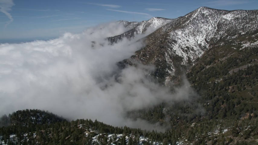 5K stock footage aerial video of clouds blanketing snowy mountain slopes in the San Bernardino Mountains, California Aerial Stock Footage | AX0009_119