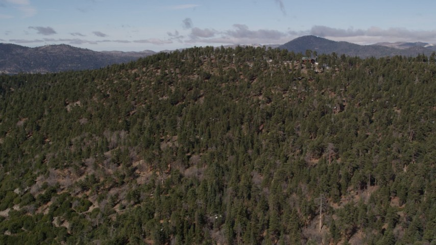 5K aerial video approach the top of a mountain covered with evergreens in the San Bernardino Mountains, California Aerial Stock Footage | AX0009_128