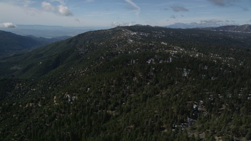 5K stock footage aerial video approach a mountain with snow patches and thick forest in the San Bernardino Mountains, California Aerial Stock Footage   AX0009_136
