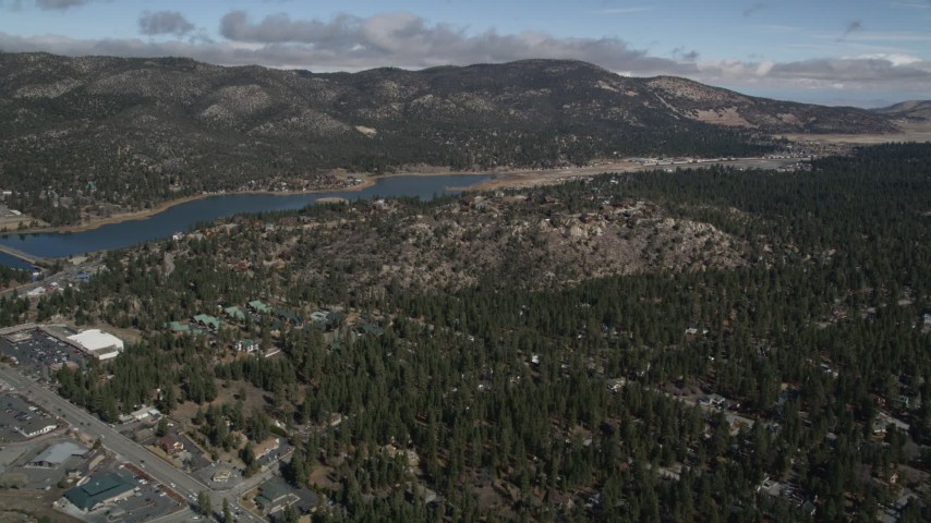 5K aerial video orbit the outskirts of the small town and the shore of Big Bear Lake in winter, California Aerial Stock Footage | AX0009_140