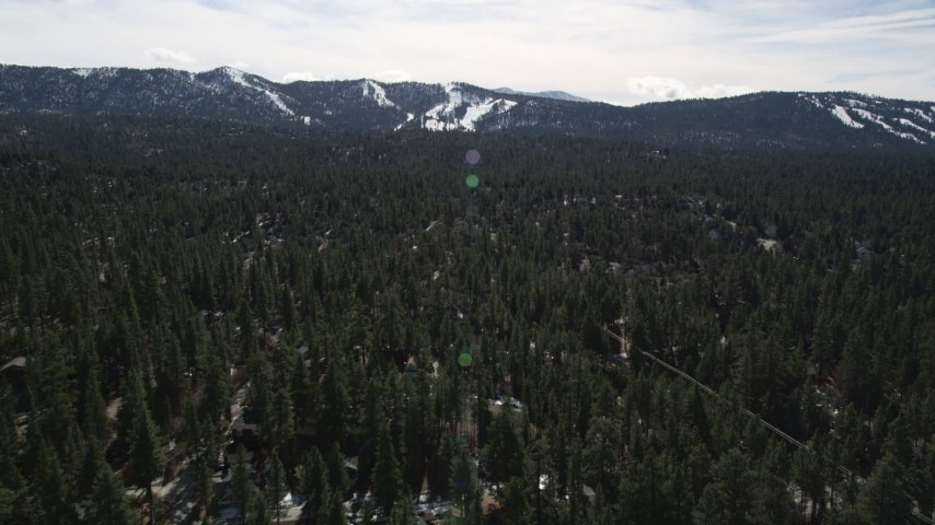 5K stock footage aerial video of Snow Summit seen from homes and trees at Big Bear Lake in winter, California Aerial Stock Footage | AX0010_003