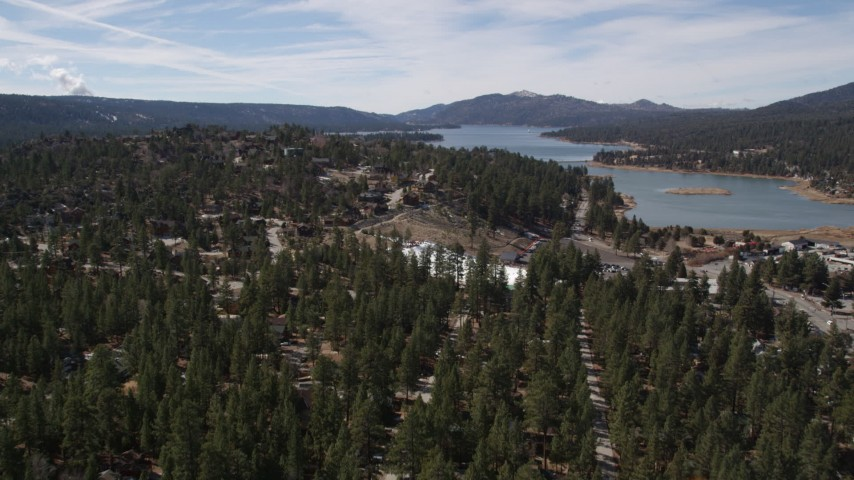 5K aerial video fly over a homes and evergreens to approach Big Bear Lake, California Aerial Stock Footage | AX0010_005