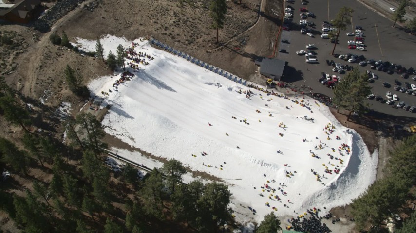 5K aerial video approach people sliding down a frozen slope at Big Bear Lake in winter, California Aerial Stock Footage | AX0010_006