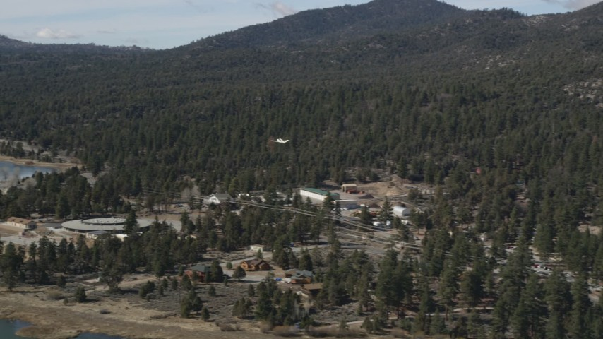 5K stock footage aerial video of tracking a small airplane approaching Big Bear Lake, California Aerial Stock Footage | AX0010_008