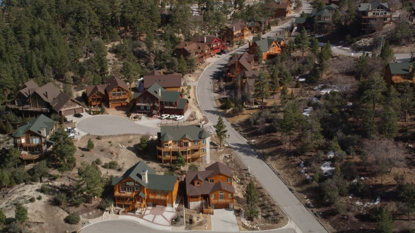 5K stock footage aerial video orbit and fly over homes near Big Bear Lake with patches of winter snow, California Aerial Stock Footage | AX0010_010