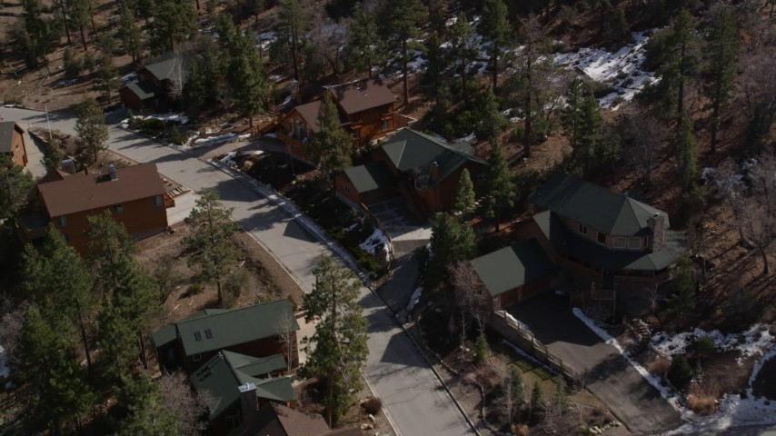 5K aerial video orbit rural homes with patches of snow at Big Bear Lake, California Aerial Stock Footage | AX0010_011