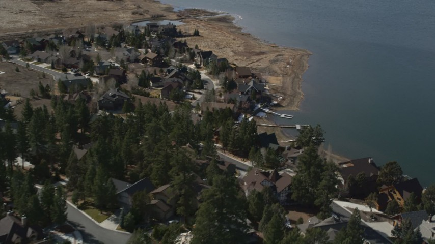 5K stock footage aerial video of orbiting lakefront homes with light snow patches at Big Bear Lake, California Aerial Stock Footage | AX0010_013
