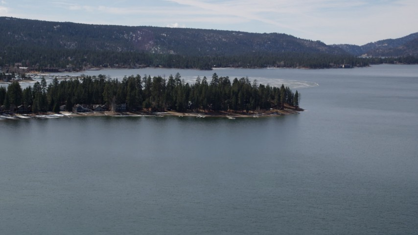 5K stock footage aerial video of approaching lakeside homes at Big Bear Lake with patches of light winter snow, California Aerial Stock Footage | AX0010_014