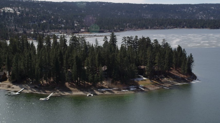 5K aerial video orbit homes on the shore of Big Bear Lake with patches of light winter snow, California Aerial Stock Footage | AX0010_015