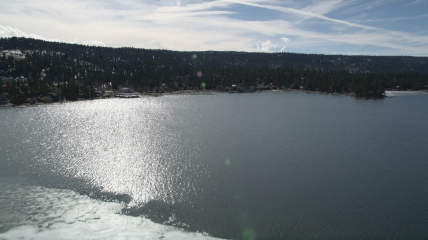 5K stock footage aerial video fly over ice patch and tilt to reveal shore of Big Bear Lake, California Aerial Stock Footage | AX0010_017