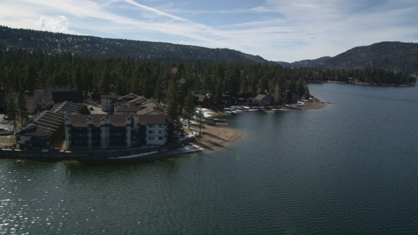 5K stock footage aerial video orbit apartment building and homes on the shore of Big Bear Lake with winter snow, California Aerial Stock Footage | AX0010_019