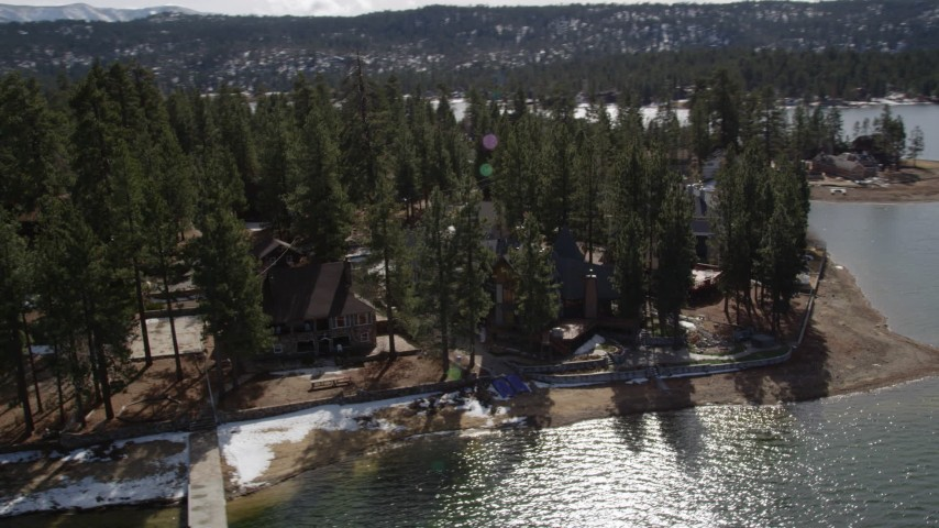 5K stock footage aerial video orbit waterfront homes with light patches of snow at Big Bear Lake, California Aerial Stock Footage | AX0010_022