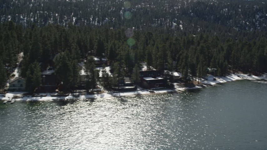 5K stock footage aerial video flyby homes on the shore of Big Bear Lake with light winter snow, California Aerial Stock Footage | AX0010_024