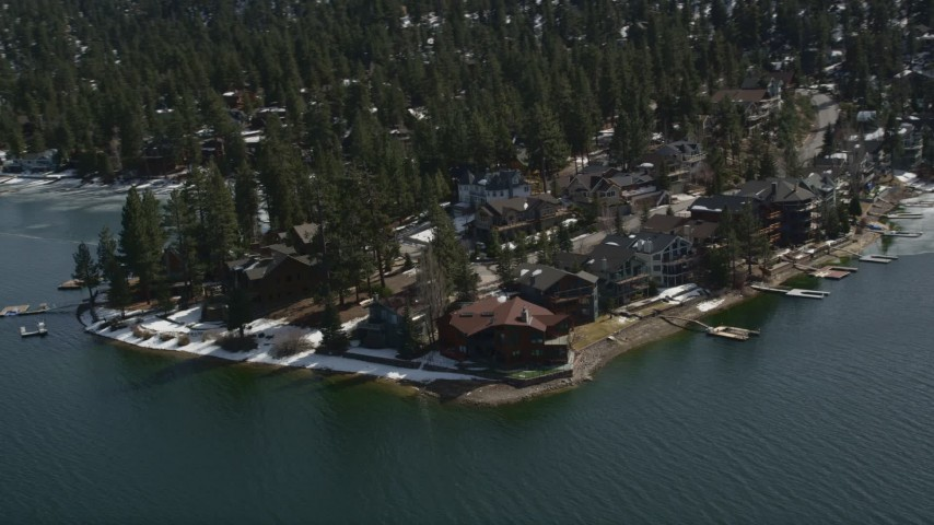 5K aerial video orbit large waterfront homes on the shore of Big Bear Lake with light winter snow, California Aerial Stock Footage | AX0010_025