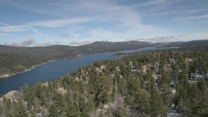 5K aerial video pan across snowy mountain and forest to reveal Big Bear Lake in winter, California Aerial Stock Footage | AX0010_028