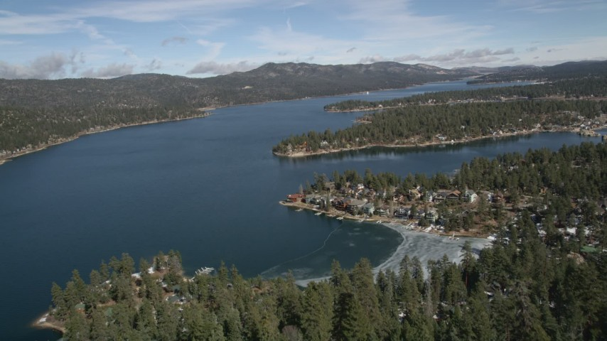5K stock footage aerial video fly over a mountain slope to reveal Big Bear Lake in winter, California Aerial Stock Footage | AX0010_029