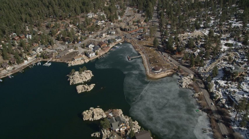 5K stock footage aerial video approach waterfront homes and the town on the shore of Big Bear Lake in winter, California Aerial Stock Footage | AX0010_031