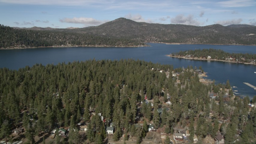 5K stock footage aerial video of Big Bear Lake seen from town on the shore in winter, California Aerial Stock Footage | AX0010_032