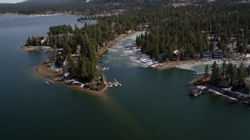 5K stock footage aerial video orbit homes on the ice shore of Big Bear Lake in winter, California Aerial Stock Footage | AX0010_034