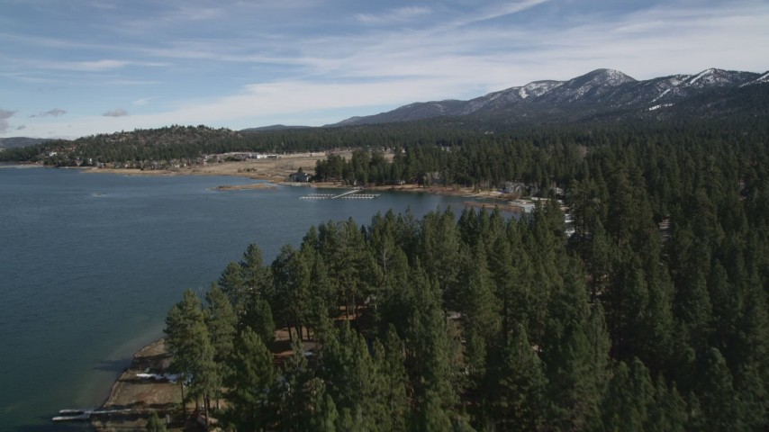 5K stock footage aerial video tilt to reveal and approach shore of Big Bear Lake with light winter snow, California Aerial Stock Footage | AX0010_036