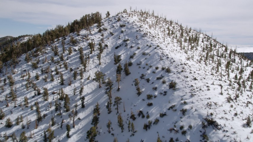 5K stock footage aerial video approach and fly over snowy peak in the San Bernardino Mountains, California Aerial Stock Footage   AX0010_066