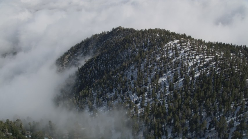 5K aerial video orbit clouds surrounding mountains with snow in the San Jacinto Mountains, California Aerial Stock Footage | AX0010_071